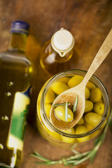 Close up green olives in bank, bottle of olive oil, rosemary on
