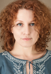 Redhead curly pretty woman with blue eyes in ethnic shirt