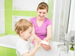 Parent and child washing hands with soap in bathroom