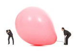 Businessmen scared balloon is inflated to burst