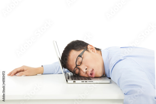 Tired overworked businessman sleeps on laptop