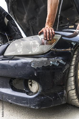 A repairman is examining the engine of the broken car