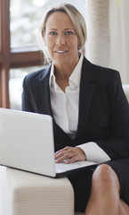 Businesswoman At Home Office Using Laptop