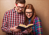 young couple in clothes and stylish hipster glasses reading a bo