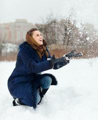 Happy girl throwing  snowflakes i