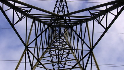 High voltage transmission tower top zoom in from bottom