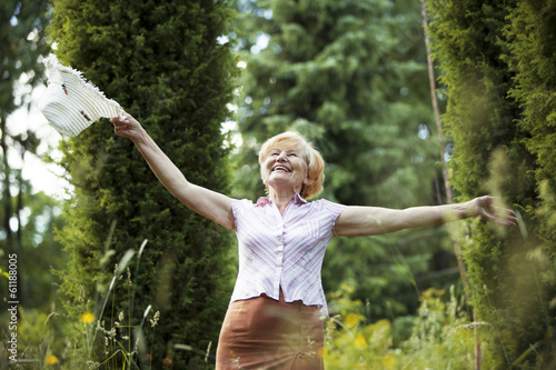 Freedom. Old Lady with Hut smiling in The Garden. Lifestyle