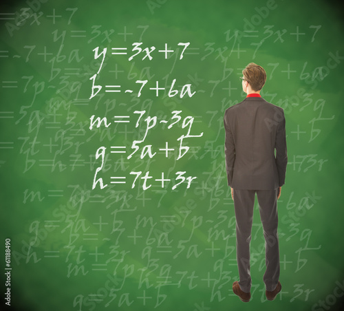 Young student looking at chalkboard with mathematics
