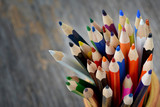 Colorful pencils in ceramic boot on wood background