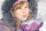 beautiful girl holding a snow and blowing on it