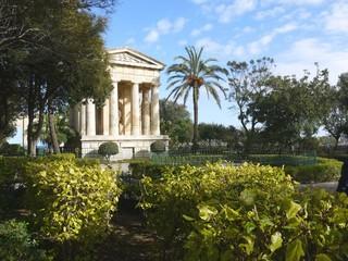 Antic monument in green garden, La Valleta, Malta