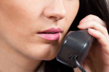 Close-up of business woman's lips with landlines phone