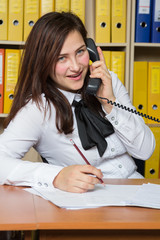 cute young office worker talking on landlines phone in office