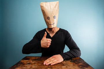 Man with bag over head giving thumbs up