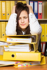 Young secretary distressed with a lot of documents on her desk