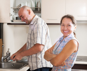 man and woman washing dishes