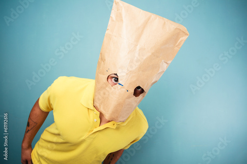 Young man with bag over head looking at camera