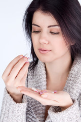 a girl looking at a pill and holding a tablet in her hands