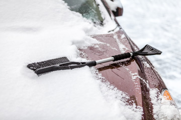 Closeup photo of black brush lying on car covered in snow