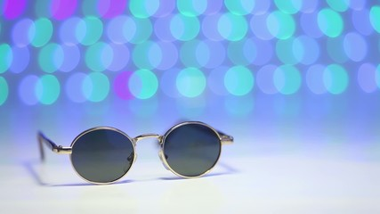 Retro brown sunglasses with blurry colored background