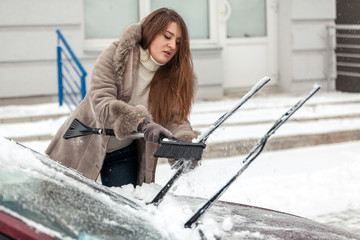 beautiful woman cleaning car with brush after blizzard
