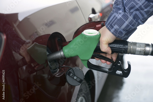 man hand refilling up gas tank of the car