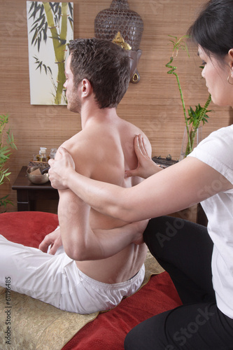 Pressure point massage - man with female masseur in original tha