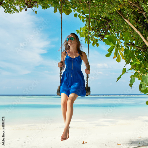 Woman in blue dress swinging at beach