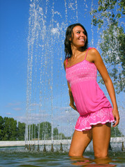 young attractive woman cooling in the fountain