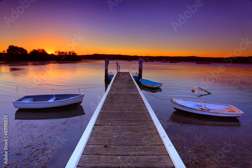 Sunset moorings and boat jetty in a little cove Australia - 61198835
