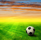 soccer ball on grass in the sunset