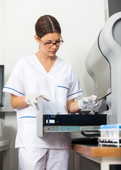Researcher Loading Samples Into Analyzer In Lab