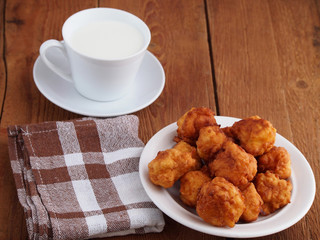 Homemade fritters and cup of milk