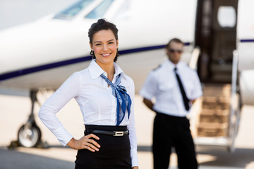 Beautiful Airhostess With Hand On Hip At Airport Terminal
