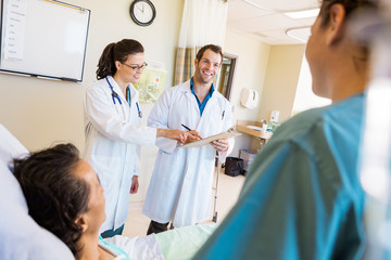 Happy Doctors Discussing Notes With Patient And Nurse In Foregro