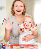Happy young mother and child with painted hands.