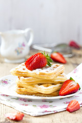 Waffles with sugar and strawberries for breakfast