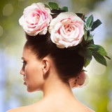 Rear view portrait of the woman with pink flowers in hairs