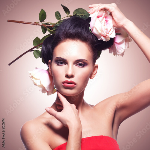 Portrait of beautiful young woman with flowers in hair.