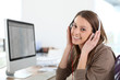 Woman in front of desktop computer with headphones