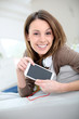 Smiling young woman websurfing with smartphone
