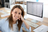 Smiling woman in office sitting at desktop