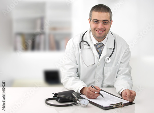 Arabian doctor in his office writing notes in his office.