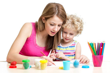 Mother and kid girl painting together