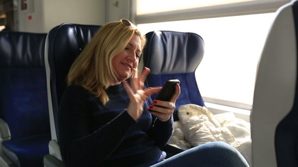 attractive blonde women using smartphone in a train