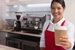 Happy young barista offering cup of coffee to go smiling at