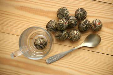 Chinese green tea balls with jasmine flowers, tea cup