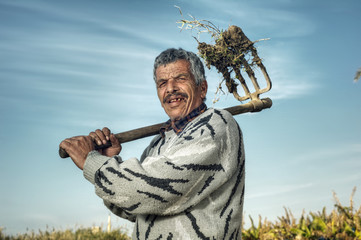 Senior Farmer holding hay fork in the fields