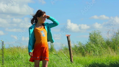 girl stands on the shore in the grass