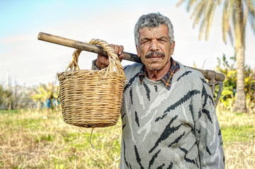 Senior farmer holding a fork and a straw basket in the fields